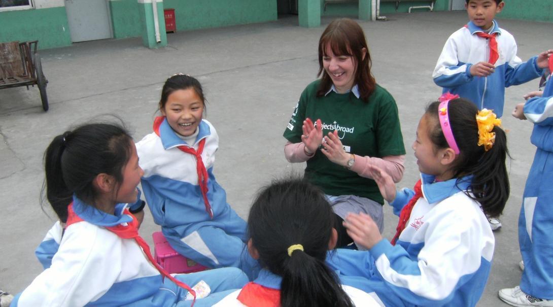 Projects Abroad vrijwilliger werkt met kinderen in China en speelt op de speelplaats in een kleuterschool.